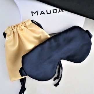 An image of the golden sating pouch over a Mauda branded cushion box. A blue satin sleep mask is partially placed over the pouch.