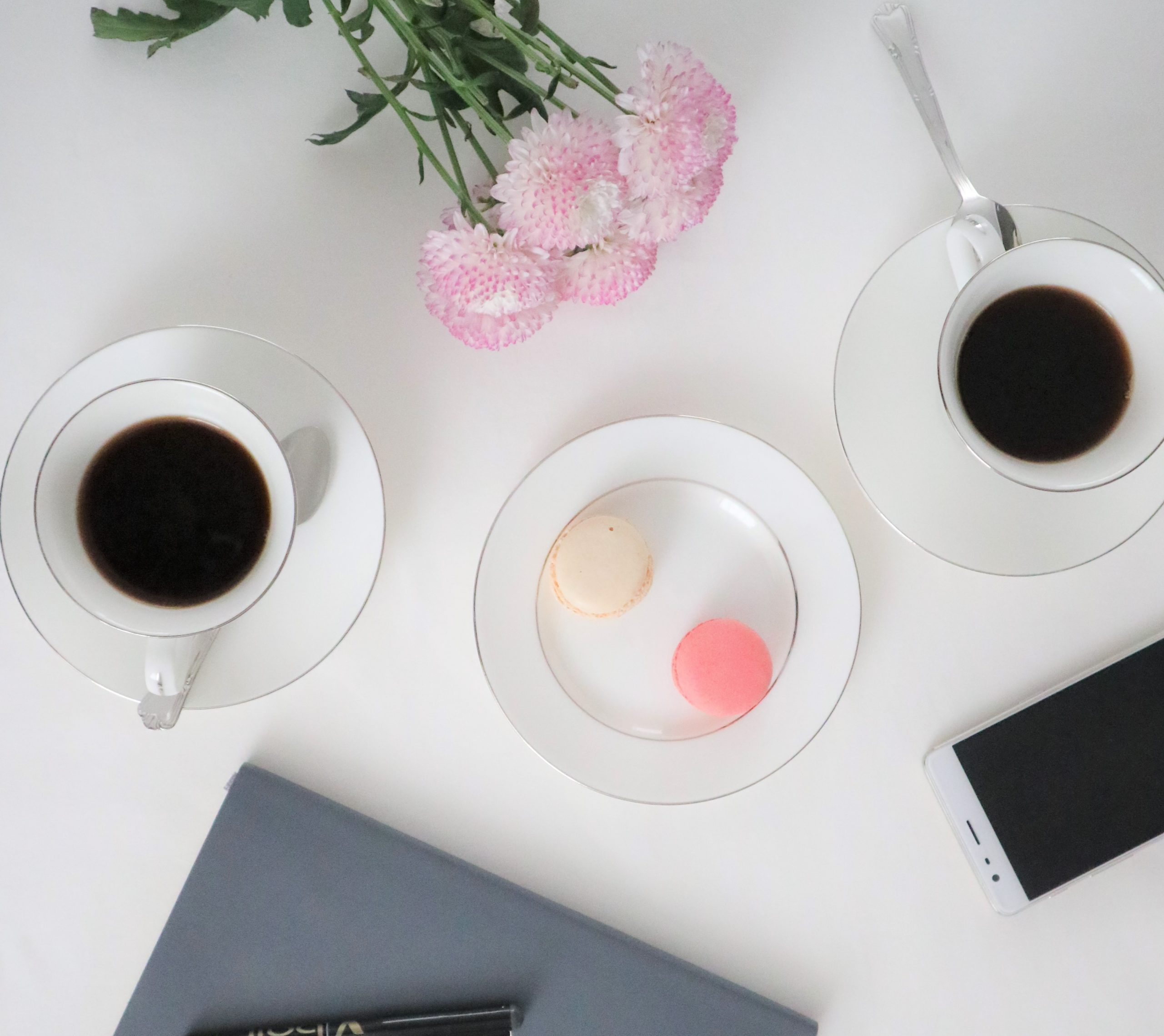 A white table with two coffee cups with saucer and spoons. There's a plate with a pink macaron and a beige macaron. Partial view of pink flowers, a notebook and pen and a mobile phone. The image suggests a setting for a face2face meeting.