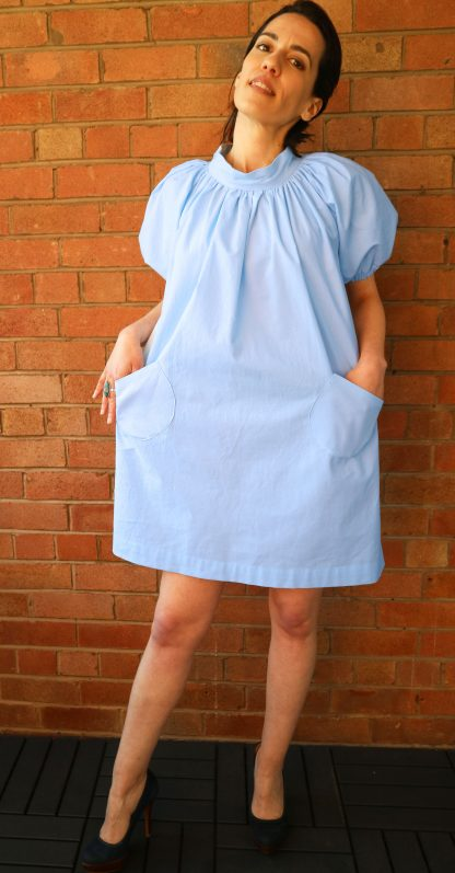 An A-line knee length dress. It ties at the back with a button which can be a standard or magnetic button. The dress has an elastic belt in loop and short puff sleeves.