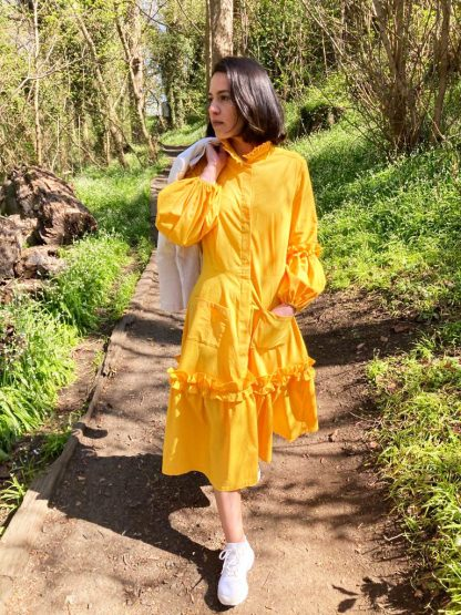 A yellow buffet dress with ruffled trims around the elbow and knees. The placket goes from the collar to the knees and you can opt from a range of available fastenings. The sleeves are puffed from the elbow to the wrist.