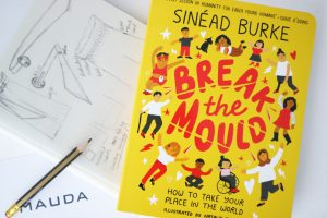 """A picture of the cover of Sinead Burke's """"Break the mould"""" book next to a sketch of Mauda's Frances Trousers, a pencil and a white card with the word """"Mauda"""" printed in black."""