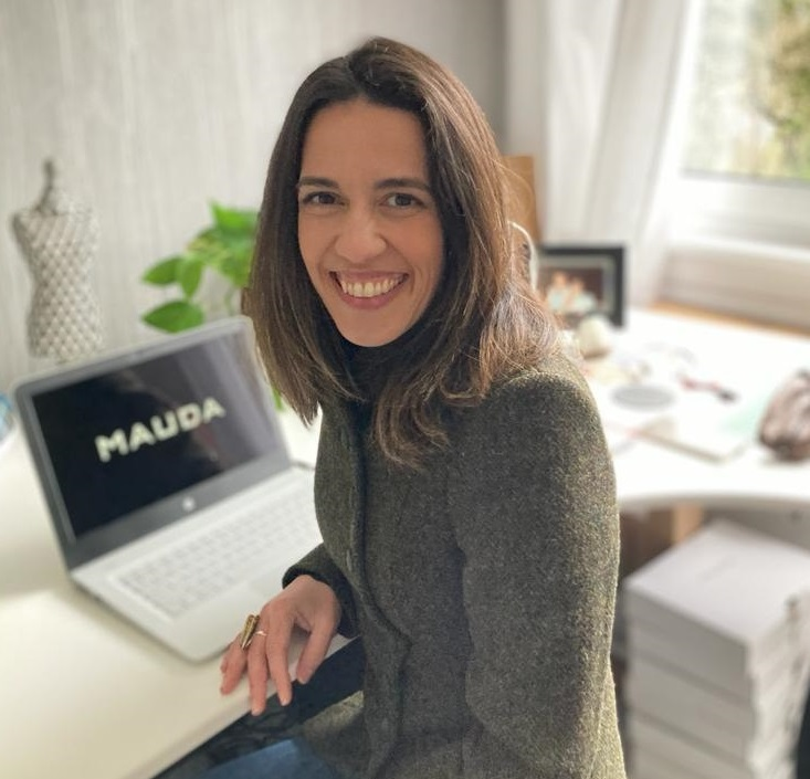 A phot of Carla Darling, founder of Mauda at her desk in her home-studio. There's a laptop with the Mauda logo over a black background and some stationery over and underneath the desk.