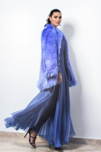 A white woman posing sideways. She has dark hair tied at the back in a ponytail. She's wearing a pleated blue skirt and a blue-violet fur coat.