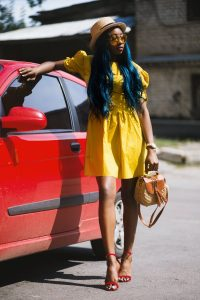 A black woman posing beside a red car. She's wearing a knee-length vibrant yellow dress with puff sleeves. She's also wearing strap red sandals and a beige hat. She's holding a handbag. Her hair is dyed in a dark blue shade, which makes a contrasting effect with the outfit.