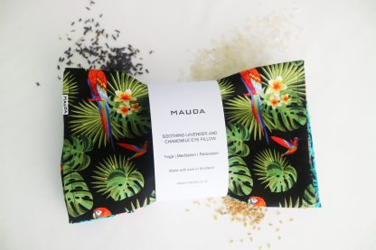 An eye pillow in a printed pattern with plants and parrots. Securing it in the middle there's a white paper with the text: Mauda. SOOTHING LAVENDER AND CHAMOMILE EYE PILLOW. Yoga, Meditation, Relaxation. Made with care in Scotland. www.mauda.co.uk
